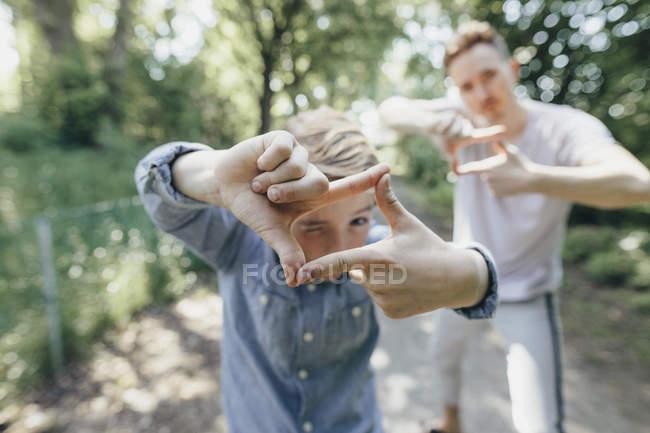 Мальчик и юноша делают рамку пальца на лесной тропе — стоковое фото