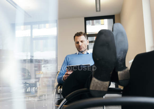 Casual businessman using tablet in office — Stock Photo