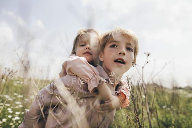 Retrato de niño dando a su hermana pequeña un paseo a cuestas - foto de stock