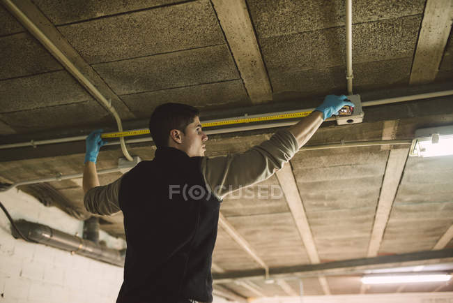 Man working on conduit at the ceiling measuring with a tape measure — Stock Photo