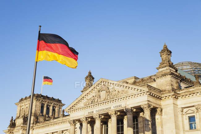 Deutschland, Berlin, Regierungsviertel, Reichstagsgebäude mit Deutschlandfahnen — Stockfoto
