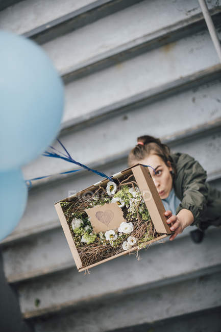 Woman sending present in cardboard box with balloons — Stock Photo