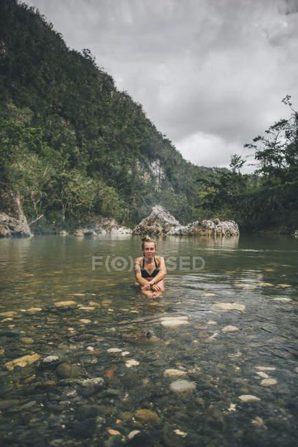 Cuba, Baracoa, Young woman sitting in Yumuri river — Stock Photo