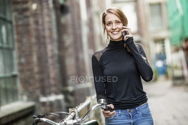 Porträt einer lächelnden Frau mit Fahrrad am Telefon — Stockfoto