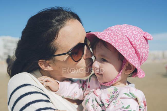 Mère embrasser bébé fille sur la plage — Photo de stock