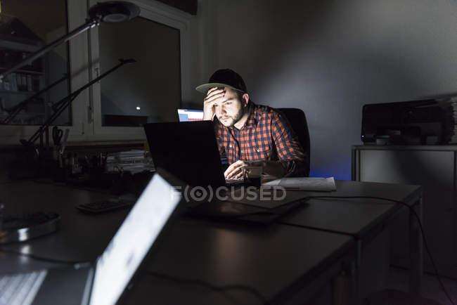 Portrait de pigiste assis au bureau travaillant sur ordinateur portable la nuit — Photo de stock