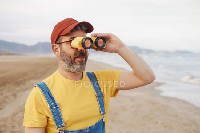 Бородатий чоловік, використовуючи Біноклі на пляжі — стокове фото