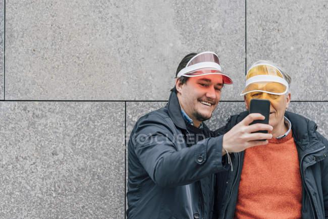 Улыбающийся молодой человек и пожилой человек в солнечных козырьках делают селфи — стоковое фото