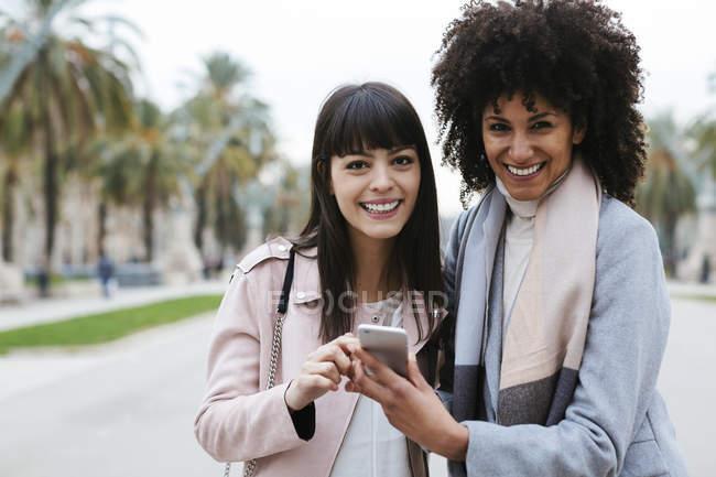 Spagna, Barcellona, due donne felici che condividono il cellulare sul lungomare — Foto stock