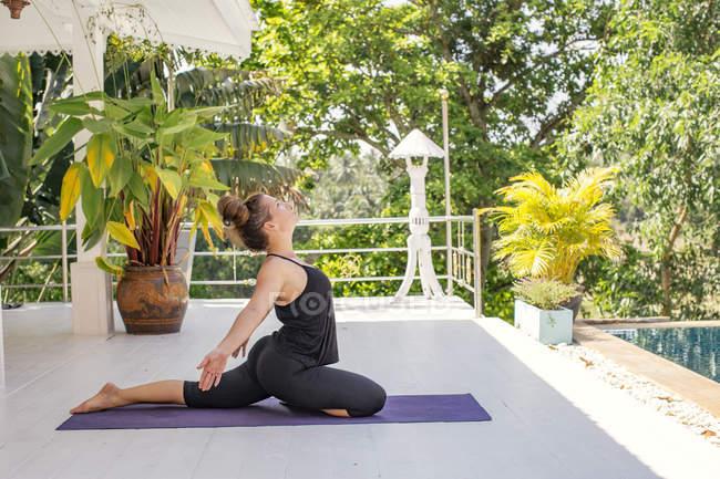 Женщина практикует йогу на террасе у бассейна — стоковое фото
