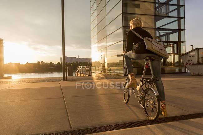 Femme âgée avec vélo de ville au bord de la rivière au coucher du soleil — Photo de stock