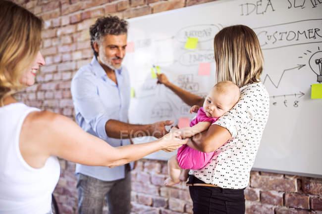 Onorevoli colleghi accarezzando bambino di lavoro materno in ufficio — Foto stock