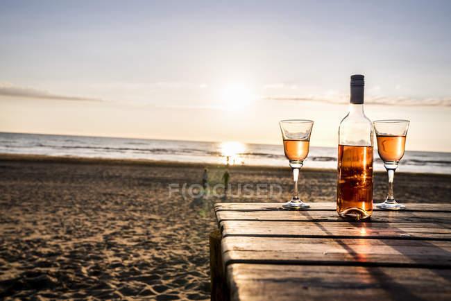 Пляшка вина і окуляри на променаду на пляжі на заході сонця — стокове фото