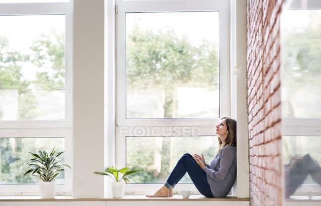 Donna seduta a casa sul davanzale della finestra, a leggere un libro — Foto stock