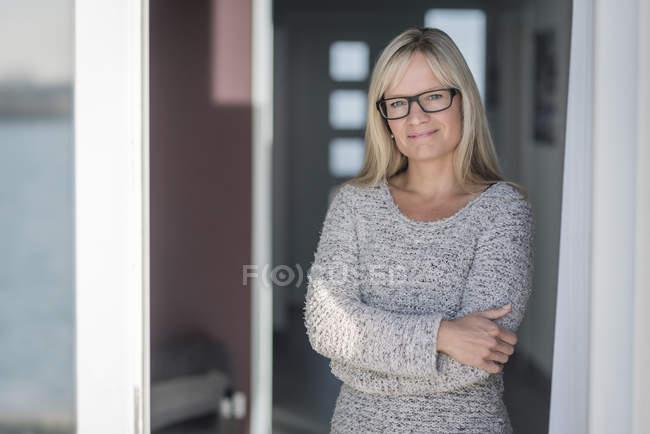 Mujer con cristales en la puerta con brazos cruzados - foto de stock