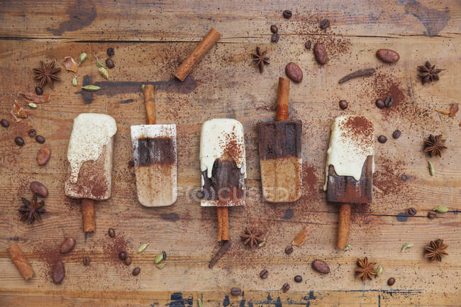 Homemade coffee and white chocolate ice lollies with winter spices on wooden background — Photo de stock