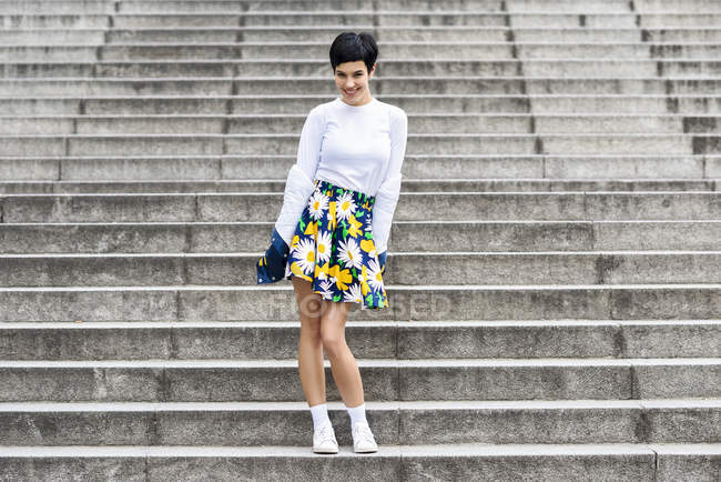 Fashionable young woman wearing skirt with floral design standing on stairs — Stock Photo