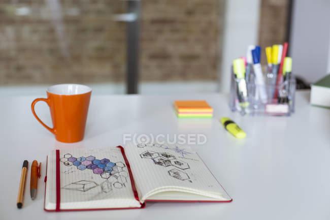 Carnet avec croquis et tasse de café sur le bureau — Photo de stock