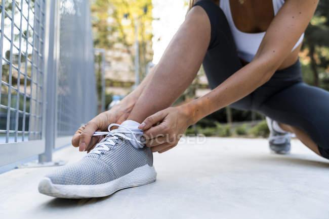 Primer plano de la mujer deportiva atándose los zapatos antes del entrenamiento - foto de stock