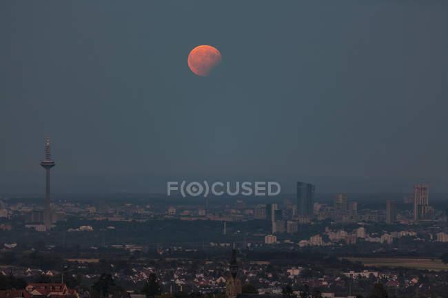 Германия, Гессен, Hochtaunuskreis, Полнолуние с частичным затмением, поднимающимся над городом Франкфурт — стоковое фото