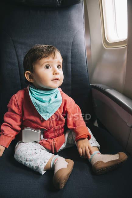 Ребенок, сидящий в самолете рядом с окном с пристегнутым ремнем безопасности — стоковое фото