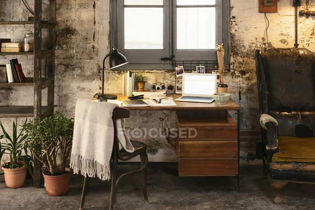 Старий стіл з ноутбуком у мансарді — стокове фото
