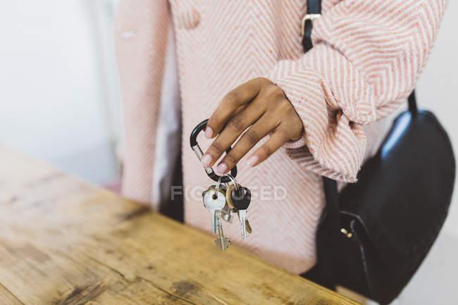 Imagen recortada de la mujer poniendo llaves en la mesa - foto de stock