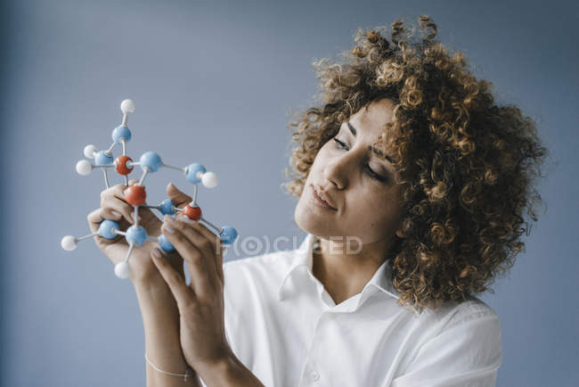 Female scientist looking at molecule model, looking for solutions — Stock Photo