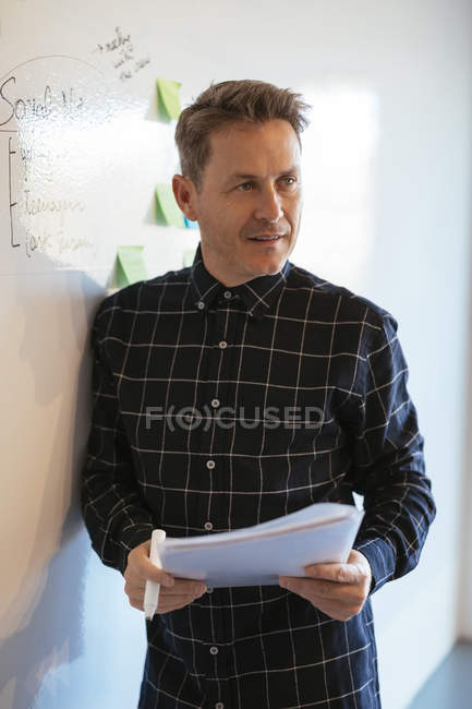 Businessman in office leaning against whiteboard — Stock Photo