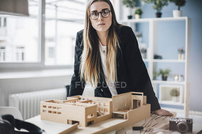 Portrait of serious architect with architectural model in office — Stock Photo