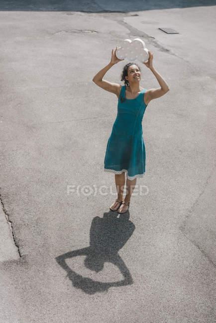 Mulher de pé no quintal, segurando símbolo de nuvem em alta voz, sorrindo — Fotografia de Stock