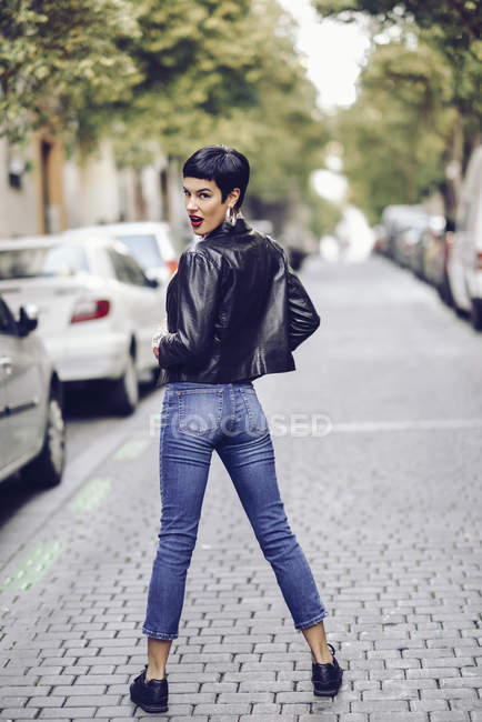 Fashionable young woman wearing jeans and leather jacket standing on street — Stock Photo