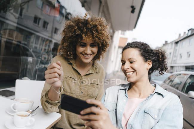 Два друга, работающие в коворкинге, сидящие за столом с кофе, используя смартфон — стоковое фото