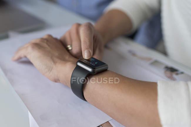 Женская рука регулирует умные часы за столом — стоковое фото