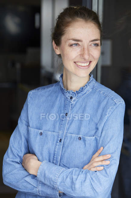 Portrait of smiling woman wearing denim shirt leaning against open window — Stock Photo