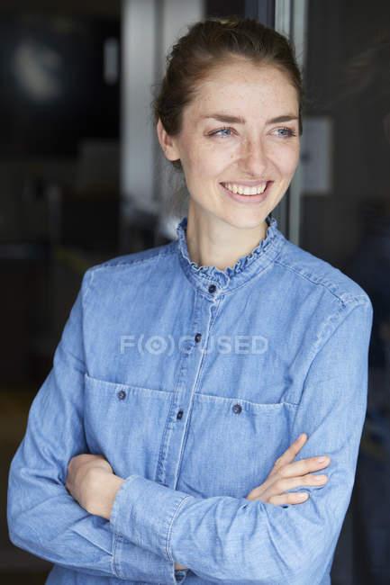 Портрет усміхненої жінки, одягненої в джинсову сорочку, притулившись до відкритого вікна. — стокове фото