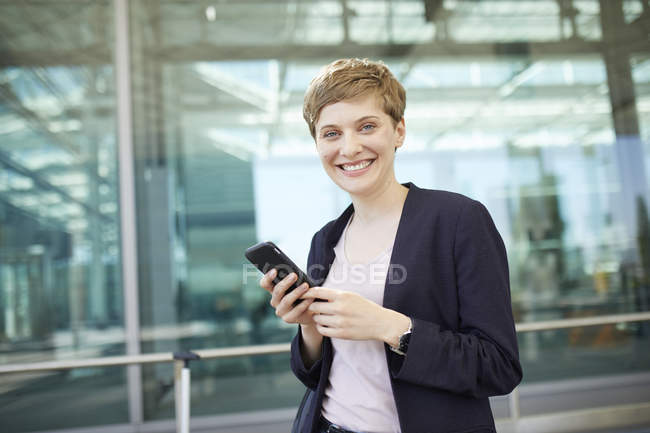 Portrait of blond businesswoman using smartphone — Stock Photo