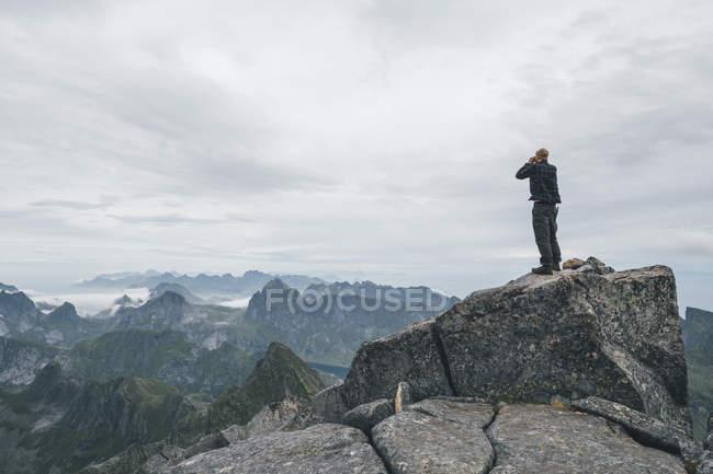 Norvège, Lofoten, Moskenesoy, Jeune homme debout à Hermannsdalstinden, regardant au-dessus du Kjerkefjord — Photo de stock