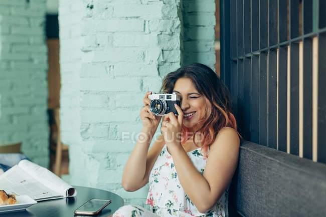 Smiling woman sitting in coffee shop taking pictures with camera — Stock Photo