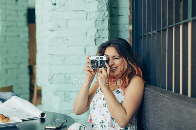 Mulher sorridente sentada no café tirando fotos com câmera — Fotografia de Stock