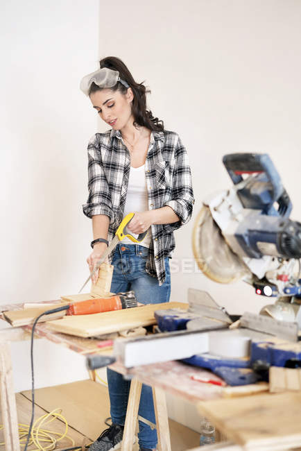 Young woman renovating her new flat, sawing piece of wood — Stock Photo