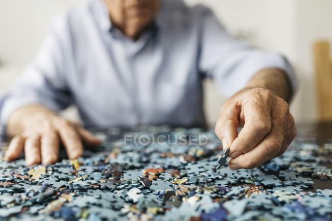 Старший чоловік робить головоломки — стокове фото