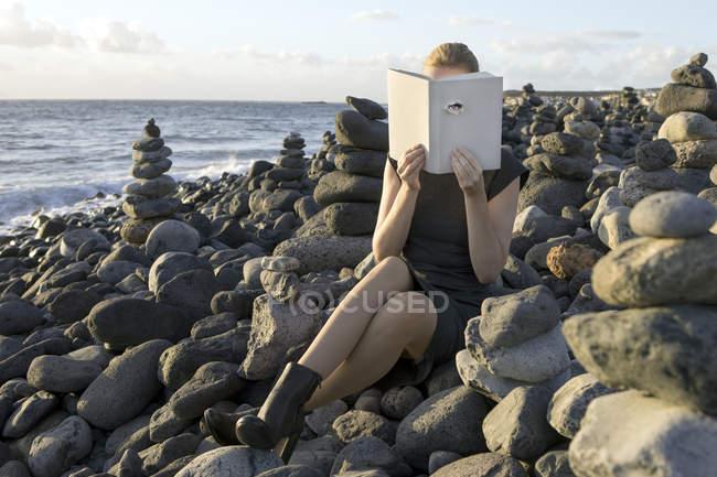 Mujer cubriendo la cara con libro, leyendo poesía, mirando a través de la cubierta - foto de stock