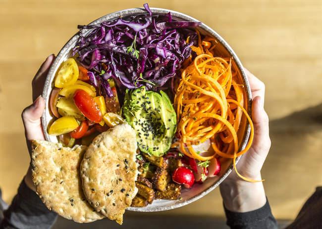Mädchen hält Vegetarische Schale mit Tomaten, Tofu, Rotkohl, Avocado, Karotten, rot rötlich, Kresse, schwarzer Sesam und Pita-Brot — Stockfoto