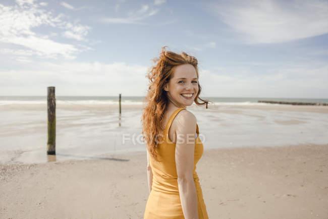 Retrato de una mujer pelirroja, riendo felizmente en la playa - foto de stock
