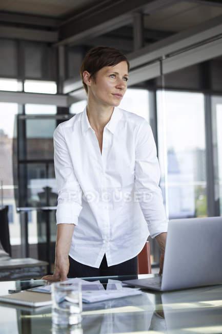 Підприємець стоячи за склом стіл в офісі з ноутбуком дивлячись боком — стокове фото