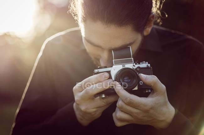 Young man photographing with analogue camera — Stock Photo