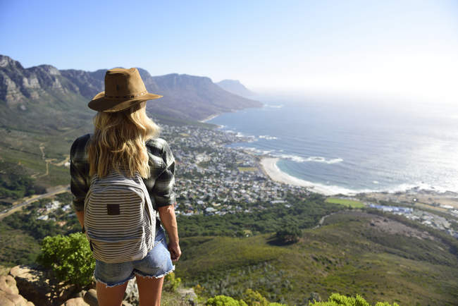 Sudáfrica, Ciudad del Cabo, mujer de pie mirando la costa durante el viaje de senderismo a Lion 's Head - foto de stock