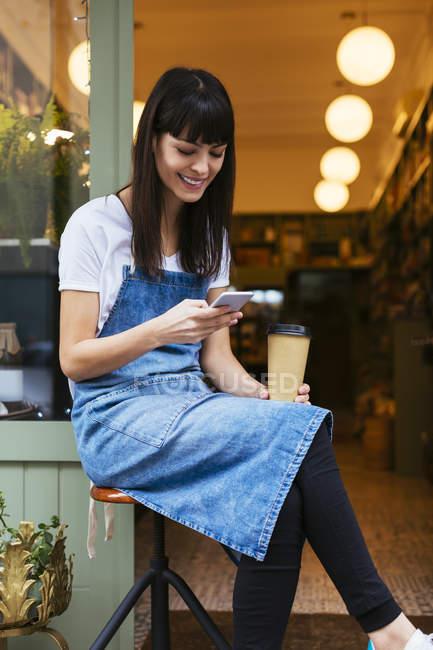 Femme souriante assise sur un tabouret en utilisant un téléphone portable à la porte d'entrée d'un magasin — Photo de stock