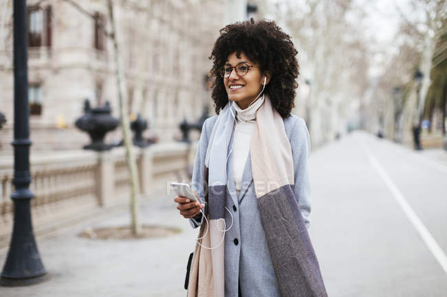 Spanien, Barcelona, lächelnde Frau mit Handy und Kopfhörer in der Stadt — Stockfoto